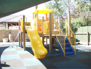 Modular playground incorporating a wavy slide installed in a Pre School