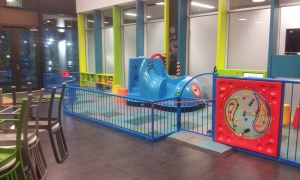 An indoor play area in a Dunedin cafe, featuring a blue boot slide